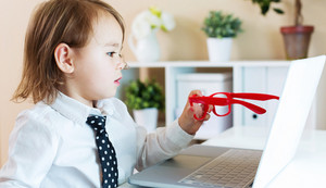 Smart little toddler girl wearing big red glasses while using her laptop