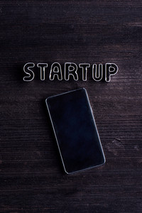 Smart phone and start up sign made of cookie cutters. Studio shot on dark wooden background. Flat lay. Copy space.
