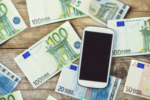 Smartphone and European currency banknotes scattered on the wooden table background. View from above.