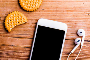 Smartphone, earphones and biscuits laid on an old office desk, flat lay, copy space
