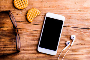 Smartphone, earphones, eyeglasses and other objects laid on an old office desk, flat lay, copy space