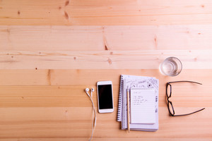 Smartphone, earphones, glass of water and eyeglasses laid on office desk. Desk with gadgets and office supplies. Studio shot on wooden background. Flat lay, empty copy space.
