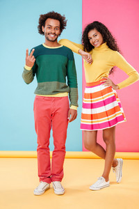Smiling african american young couple showing peace sign over colorful background