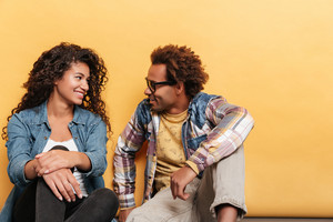 Smiling african american young couple sitting together over yellow background