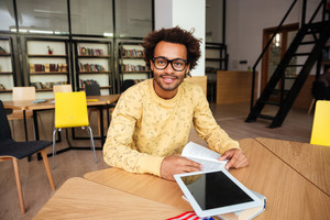 Smiling african american young man in glasses with blank screen tablet sitting in library