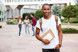 Smiling african american young man student with backpack standing outdoors