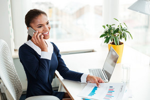 Smiling African business woman in dress sitting by the table and talking on phone in office