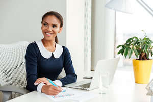 Smiling african business woman in dress sitting by the table and writing something in notebook on workplace