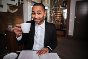 Smiling African man in suit sitting with journal and coffee in hotel and looking at camera