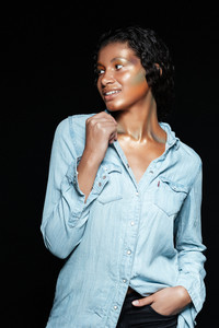 Smiling african model in shirt in studio. looking away. isolated black background