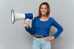 Smiling african woman holding megaphone in one hand and second hand at hip. Isolated gray background