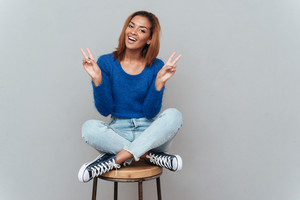 Smiling african woman in sweater and jeans sitting on chair and showing peace. Isolated gray background