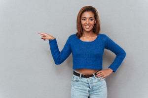Smiling african woman in sweater showing finger away and holding second hand at hip. Girl looking at camera. Isolated gray background