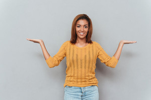 Smiling african woman in yellow sweater and jeans choosing between copyspace as well as looking at camera. Isolated gray background