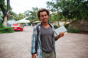 Smiling african young man with backpack standing and holding books outdoors