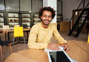 Smiling african young man with blank screen tablet sitting at the table and reading in library