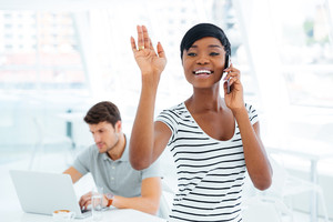 Smiling afro american businesswoman waving while talking on mobile phone in office
