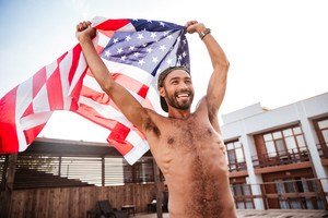 Smiling afro american shirtless man holding american flag outdoors