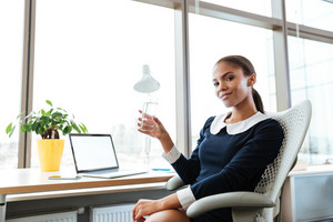 Smiling afro business woman in dress sitting by the table near the window with cup of water in hand and looking at camera in office