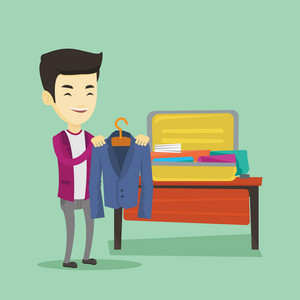 Smiling asian business man putting a suit into a suitcase. Young business man packing his clothes in an opened suitcase. Man preparing for vacation. Vector flat design illustration. Square layout.