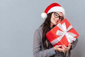 Smiling Asian girl in christmas hat holding gift in hands and looking at camera. Isolated gray background