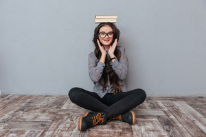 Smiling Asian woman in glasses sitting on the floor with books on head and holding hands near the cheeks. Isolated gray background