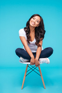 Smiling attractive asian woman sitting on the chair over blue background