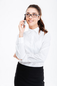 Smiling attractive young businesswoman in glasses standing and talking on mobile phone over white background