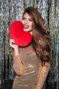 Smiling attractive young woman holding red heart over sparkling background