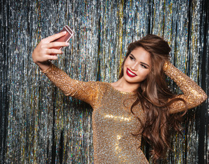 Smiling attractive young woman in evening dress taking selfie with mobile phone over shining background