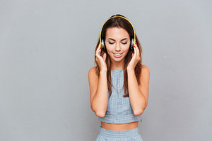 Smiling attractive young woman in headphones standing and listening to music over grey background
