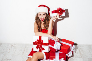 Smiling attractive young woman in santa claus costume sitting and holding present box isolated on the white background