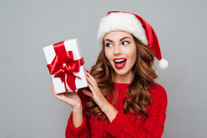 Smiling attractive young woman in santa claus hat with present box over gray background