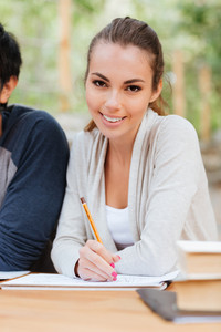 Smiling attractive young woman sitting and writing at the table