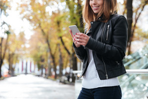 Smiling attractive young woman standing and using mobile phone in park