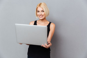 Smiling attrative young woman standing and using laptop over gray background