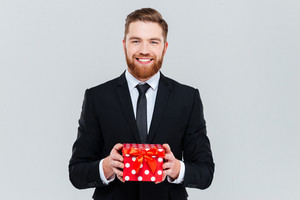 Smiling bearded business man in black suit holding gift in hands and looking at camera. Isolated gray background
