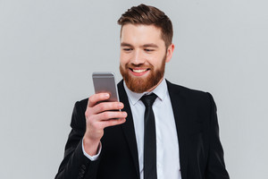 Smiling bearded business man in black suit writing message on phone in studio. Isolated gray background