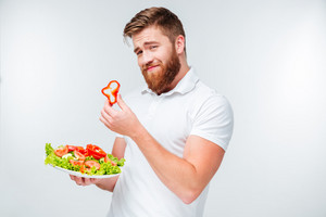 Smiling bearded man holding slice of red papper and plate with fresh salad isolated on white background