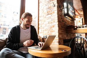 Smiling Bearded man sitting by the table with laptop computer in cafe