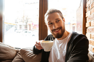 Smiling Bearded man sitting in cafe near the window with cup of coffee in hand and looking away