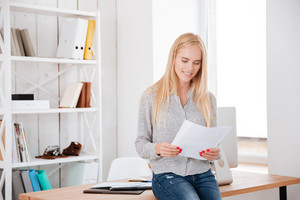 Smiling beautiful businesswoman sitting on the office desk and reading documents