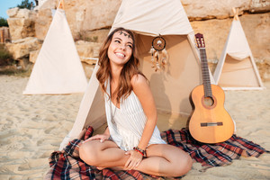Smiling beautiful hippy girl resting at the beach tent at campsite