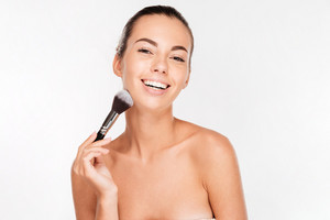 Smiling beautiful woman applying blush on face with brush tool isolated on white background