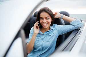 Smiling beautiful woman driving car and talking on mobile phone