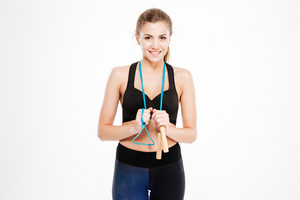 Smiling beautiful woman in sports wear standing with skipping rope isolated on a white background