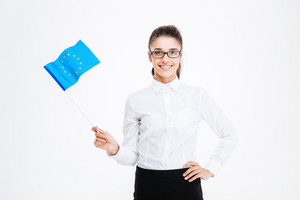 Smiling beautiful young businesswoman in glasses holding flag of european union over white background