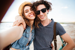 Smiling beautiful young couple hugging and taking selfie on the beach