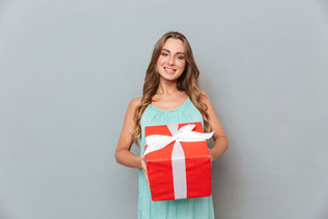 Smiling beautiful young woman holding gift box