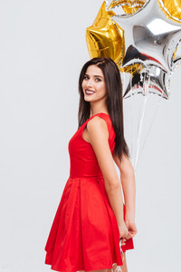 Smiling beautiful young woman in red dress standing and holding star shaped balloons over white background